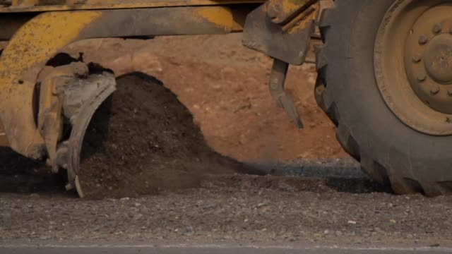 grader aligns and lays the ground on the road - dumper truck stock videos & royalty-free footage