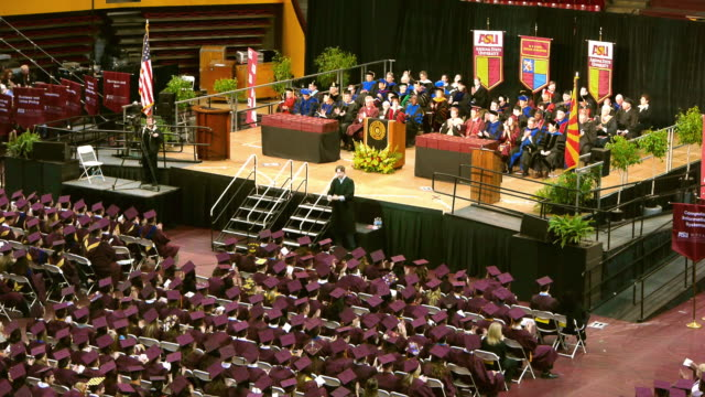 Graduates and dignitaries applaud a speaker at a Arizona State University graduation ceremony in the Wells Fargo Arena.