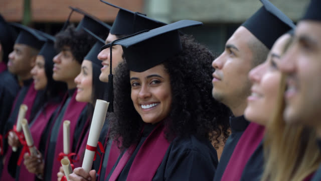 graduates standing in a line at the graduation ceremony looking away while afro young woman looks at camera smiling - studente universitario video stock e b–roll