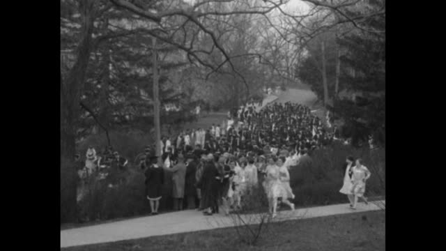 graduating seniors in gowns and caps at wellesley college running in race rolling hoops between lines of underclassmen watching them / shot from rear... - 1928 stock-videos und b-roll-filmmaterial