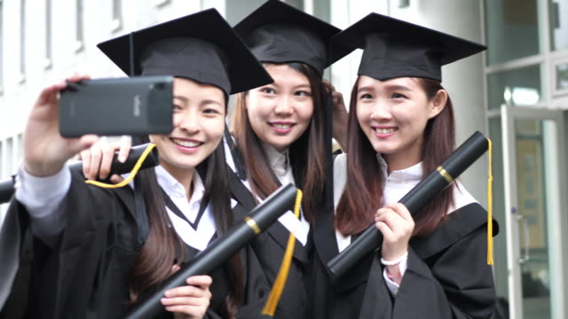 laurea in asia orientale - donne in abiti e berretti di laurea - east asian ethnicity video stock e b–roll