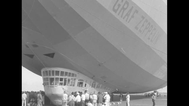 graf zeppelin crew hanging out zeppelin windows / many men helping to tether zeppelin / almost nose to tail / spectators under nose / tail with 2... - newsreel stock videos & royalty-free footage