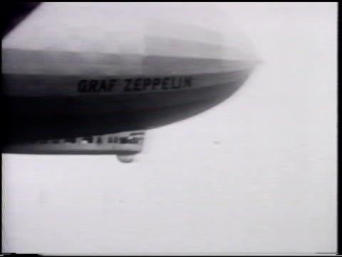 Graf Zeppelin dirigible in flight WS 'Graf Zeppelin' name on side near end AERIAL WS Passenger ship on ocean MS Passengers waving from Zeppelin...