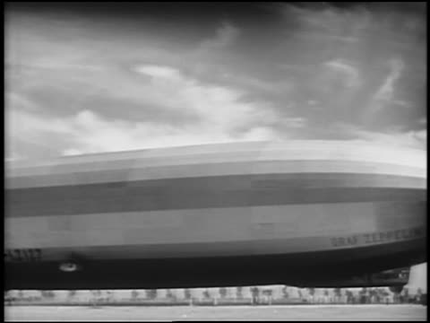 b/w 1929 pan graf zeppelin floating in air / nyc skyline in background / newsreel - 1920 1929 stock videos and b-roll footage