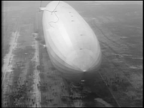 b/w 1929 aerial graf zeppelin flying very low over ground / people walk alongside / lakehurst, nj - 1920 1929 stock videos and b-roll footage