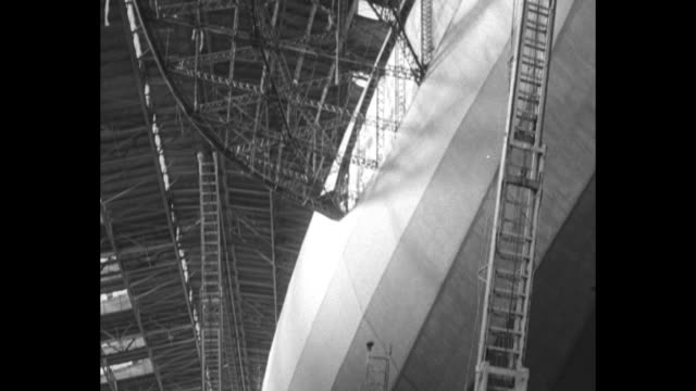 """graf zeppelin"" in hangar, airplane on ground beneath it / panning shot from below of graf zeppelin / panning shot from above of graf zeppelin and... - newsreel stock videos & royalty-free footage"