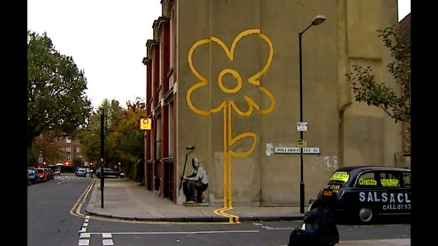 westminster council to paint over work by banksy r31100716 east london bethnal green banksy mural featuring flower painted from double yellow lines... - yellow stock videos & royalty-free footage