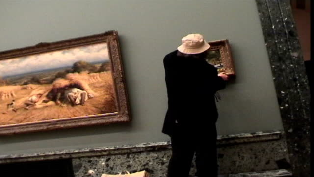 graffiti artist banksy's work auctioned at sotheby's lib london tate britain banksy disguised as an old man hanging his ersatz old master painting... - sotheby's stock videos and b-roll footage