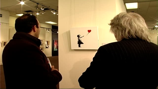 graffiti artist banksy's work auctioned at sotheby's people looking at banksy work on walls - sotheby's stock videos and b-roll footage