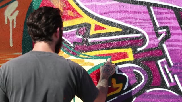 graffiti artist, david sanchez, uses spray paint to create his art on the side of a wall as the wynwood neighborhood prepares for the annual art... - joe 03 stock videos & royalty-free footage