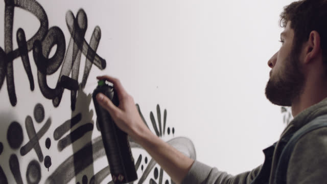 cu slo mo. graffiti artist decorates white studio wall with black spray paint words and designs. - graffiti stock videos and b-roll footage