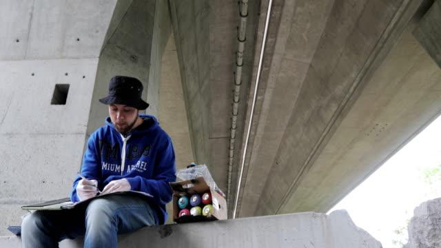 graffiti-künstler zieht eine skizze vor dem sprühen an der wand - künstlerischer beruf stock-videos und b-roll-filmmaterial