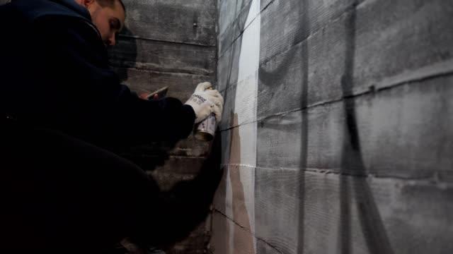 vídeos de stock, filmes e b-roll de grafiteiro fazendo um graffiti com uma pintura de pulverizador - pintor artista