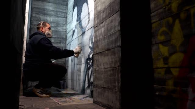 vídeos de stock, filmes e b-roll de grafiteiro fazendo arte em uma parede em algum lugar dentro de casa - pintor artista