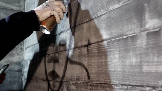 vídeos de stock, filmes e b-roll de grafiteiro fazendo linhas de contorno grafite em uma parede com lata de aerossol - pintor artista