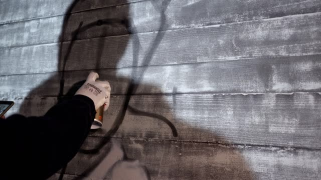 vídeos de stock, filmes e b-roll de grafiteiro pintando uma parede fazendo a arte do graffiti - pintor artista