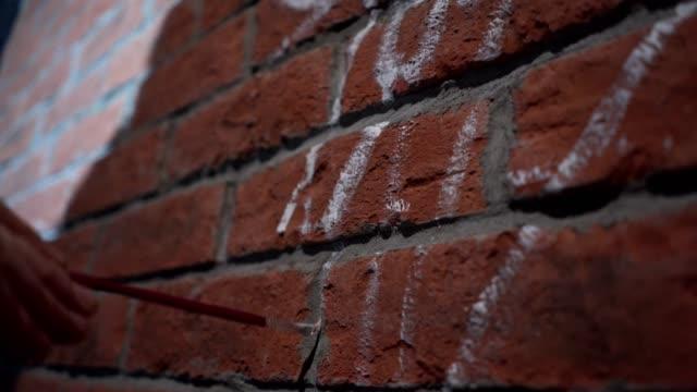 vídeos de stock, filmes e b-roll de linhas de contorno do graffiti artista pintura em uma parede de tijolo - pintor artista