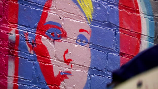 graffiti artist removes stencil from wall art - cu - painted image stock videos & royalty-free footage