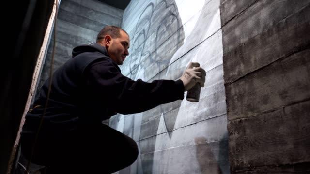 vídeos de stock, filmes e b-roll de grafiteiro sombreamento um graffiti na parede - pintor artista