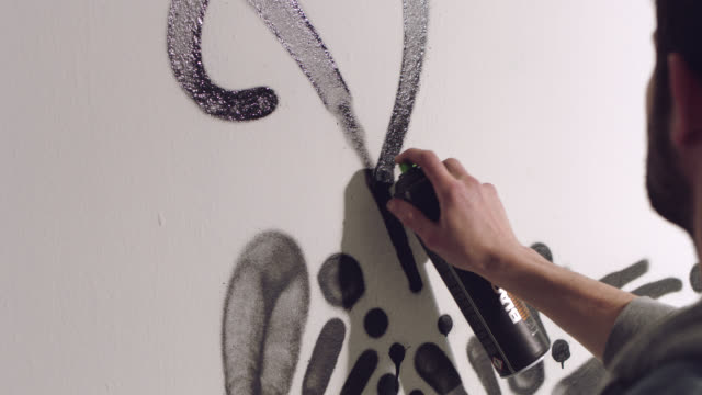 cu slo mo. graffiti artist shakes spray paint can and tags white wall with signature. - shaking stock videos & royalty-free footage