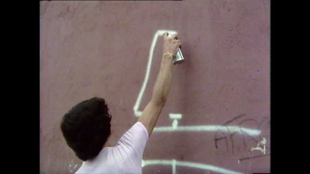 graffiti artist sketches a design on a red wall;1976 - bbc archive stock-videos und b-roll-filmmaterial