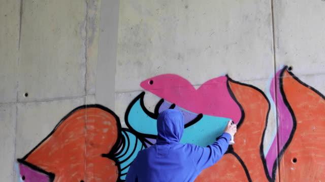 graffiti artist spraying graffiti on wall - graffiti stock videos and b-roll footage