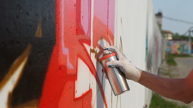 graffiti artist spraying paint on wall (hd) - spraying stock videos and b-roll footage
