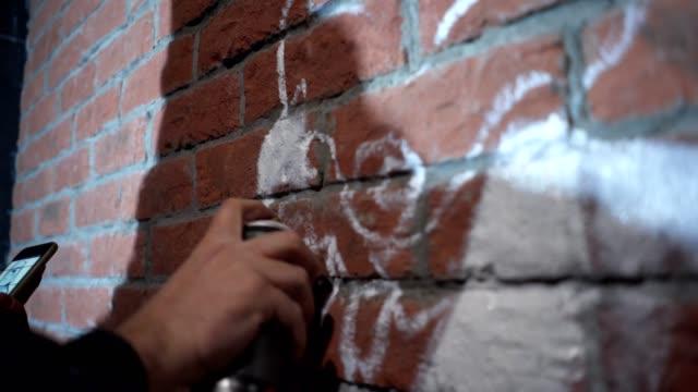 vídeos de stock, filmes e b-roll de grafiteiro usando uma tinta spray, enquanto olha para um esboço sobre um telefone móvel. - pintor artista