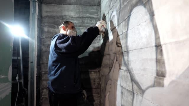 vídeos de stock, filmes e b-roll de artista de graffiti com uma máscara protetora na sua pintura de rosto em uma parede - pintor artista