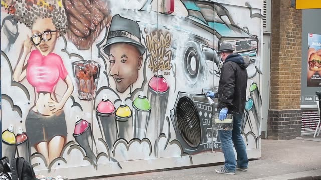 a graffiti artist works on a mural in the shoreditch area of london united kingdom on monday 30 march 2015 - hipster person stock videos & royalty-free footage