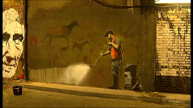graffiti artists hold cans festival good shot of cave painting by banksy - バンクシー点の映像素材/bロール