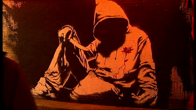 graffiti artists hold cans festival good shot of 'unknown hoodie' by banksy - バンクシー点の映像素材/bロール