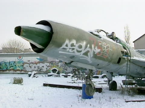 graffiti covered airplane out of date jet amp wall bg pan snow covered yard top of pink tank pointed upward against graffiti wall - drittes reich stock-videos und b-roll-filmmaterial