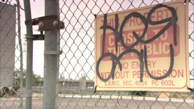 graffiti covers a sign on a chain-link fence. - chainlink fence stock videos and b-roll footage