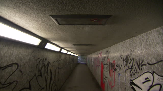 Graffiti covers the walls of a pedestrian underpass.