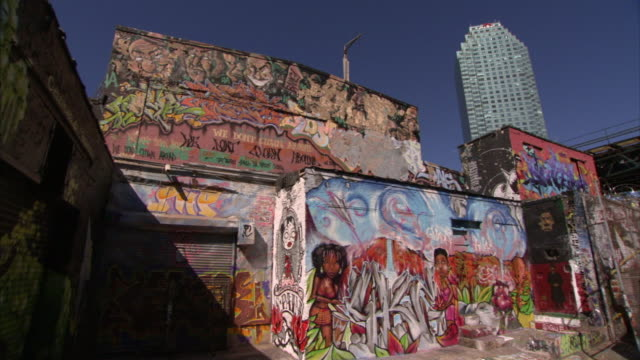 graffiti fully covers building exteriors in queens. - queens stock-videos und b-roll-filmmaterial