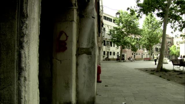 graffiti mars stone walls and a corridor in a venetian ghetto neighborhood. available in hd. - ghetto video stock e b–roll