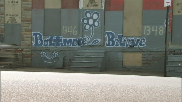 vidéos et rushes de graffiti on abandoned building wall, baltimore believes w/ single flower art, various vehicles passing through frame on street fg. md - baltimore
