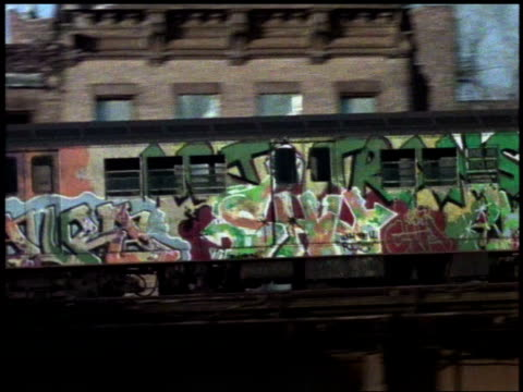1982 WS Graffiti-covered trains passing each other in opposite directions / Bronx, New York City, New York, United States