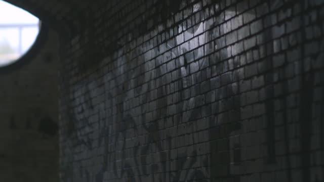 ms rf grafitting on tiled wall in derelict building  / cumberland railway station, nr. glasgow. scotland, united kingdom - differential focus点の映像素材/bロール