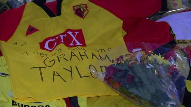 Tributes paid Watford Vicarage Road Poster 'Graham Taylor We Love You' on window PULL OUT floral tributes at makeshift memorial Various shots of...