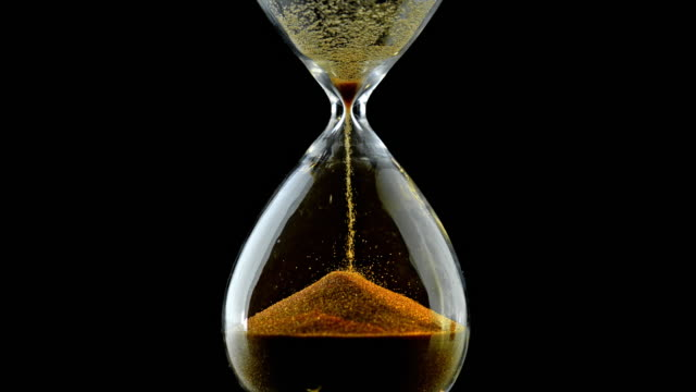 slo mo ld grains of golden sand falling through an hourglass - instrument of time stock videos & royalty-free footage