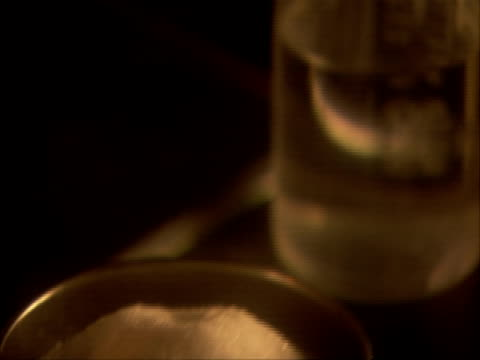 vídeos de stock, filmes e b-roll de grains of white powder placed in beaker of water and dissolve, uk (sound available) - espátula
