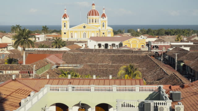 granada - nicaragua skyline from the vantage point of the bell tower la merced church. in this 4k video we can see a some roofs and yards in the foreground and the colonial style cathedral with a dome and the nicaragua cocibolca lake on the background - church stock videos & royalty-free footage
