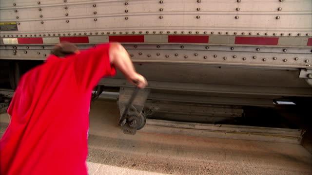 a granary worker unwinds a hopper door to receive grain. - ausgefranst stock-videos und b-roll-filmmaterial