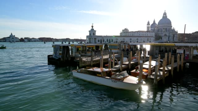 grand canal with water taxis and maria della salute church, venice, venetian lagoon, veneto, italy - 水上タクシー点の映像素材/bロール