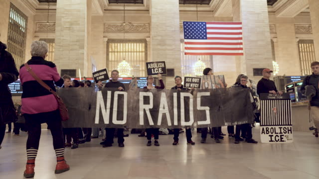 """grand central station: activist from rise and resist hold sings read """"close the camps"""" and signs that read """"abolish ice"""" . rise and resist has been... - アメリカ移民税関捜査局点の映像素材/bロール"""