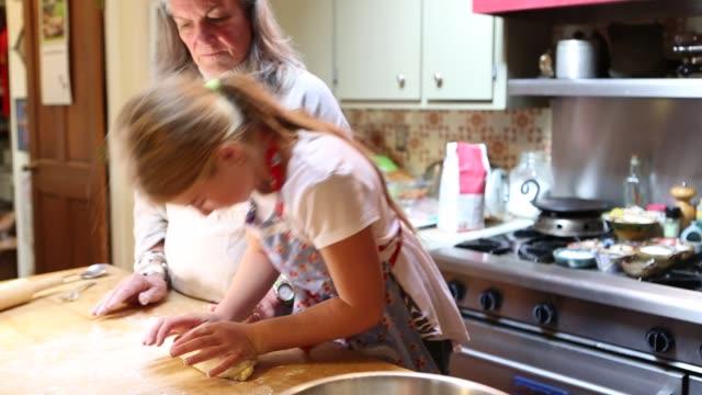 vídeos de stock e filmes b-roll de grand daughter and her grandmother rolling dough on table - família de várias gerações
