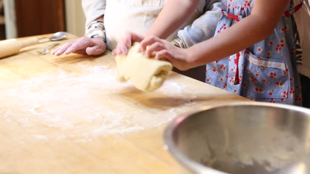 grand daughter and her grandmother rolling dough on table