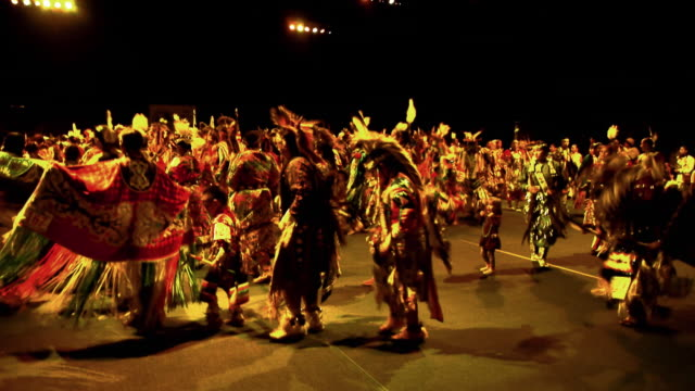 WS Grand entry ceremony at opening of Indian pow wow with hundreds of dancers in colorful parade / Indio, California, USA